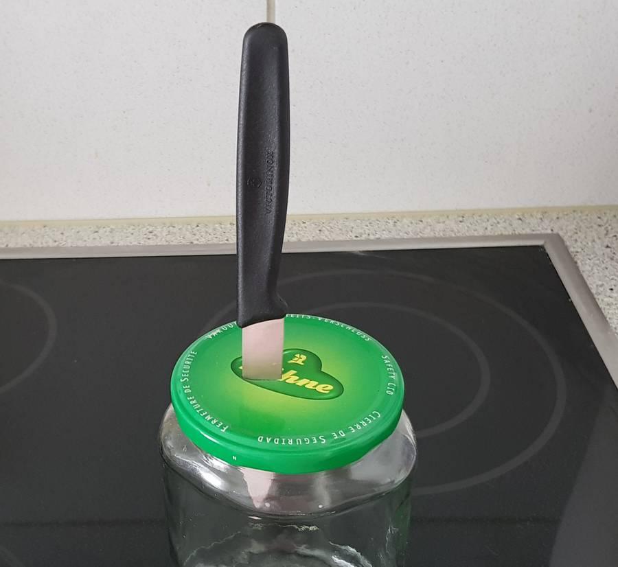 Der Gurkenglasdeckel wird mit einem Messer geöffnet.