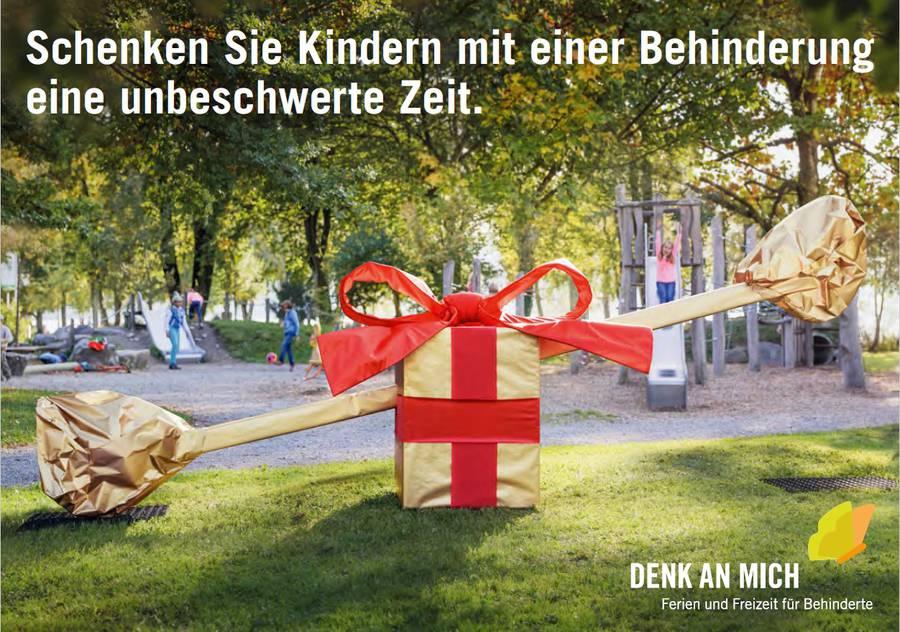 Eine Schaukeln die in Geschenkpapier eingehüllt ist und auf einem hindernisfreien Spielplatz steht.