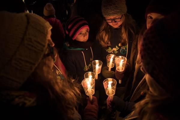 Verschiedene Kinder halten dan Friedenslicht in Händen.