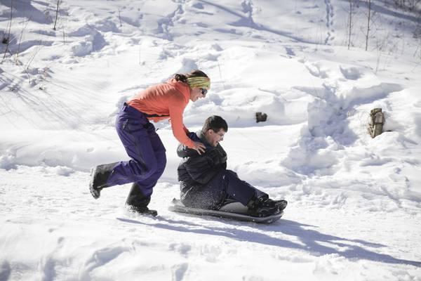 eine Frau schiebt einen Wintersportler im Bob den Hang hinunter.