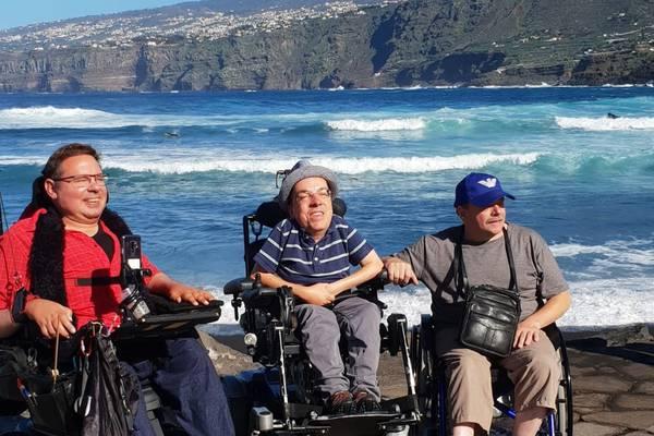 Drei Herren im Rollstuhl am Meer.