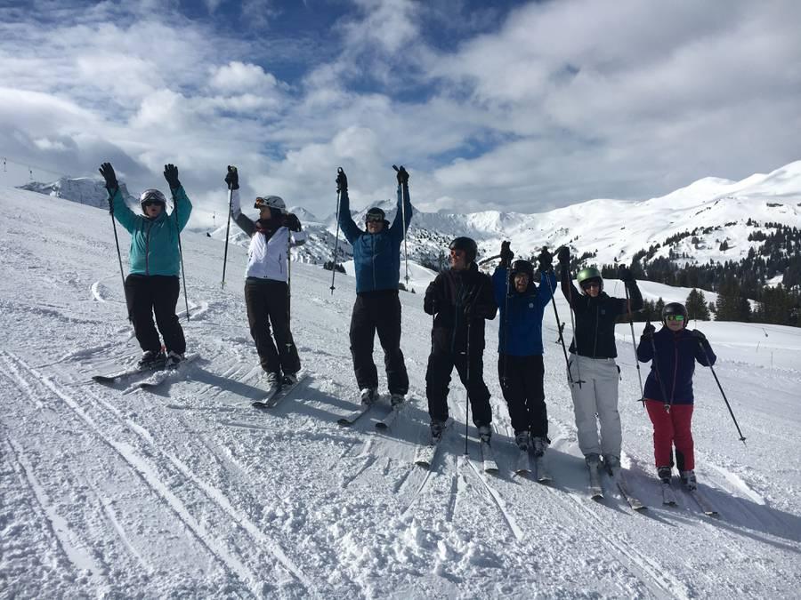 7 Skifahrende Jubeln auf der Skipiste.