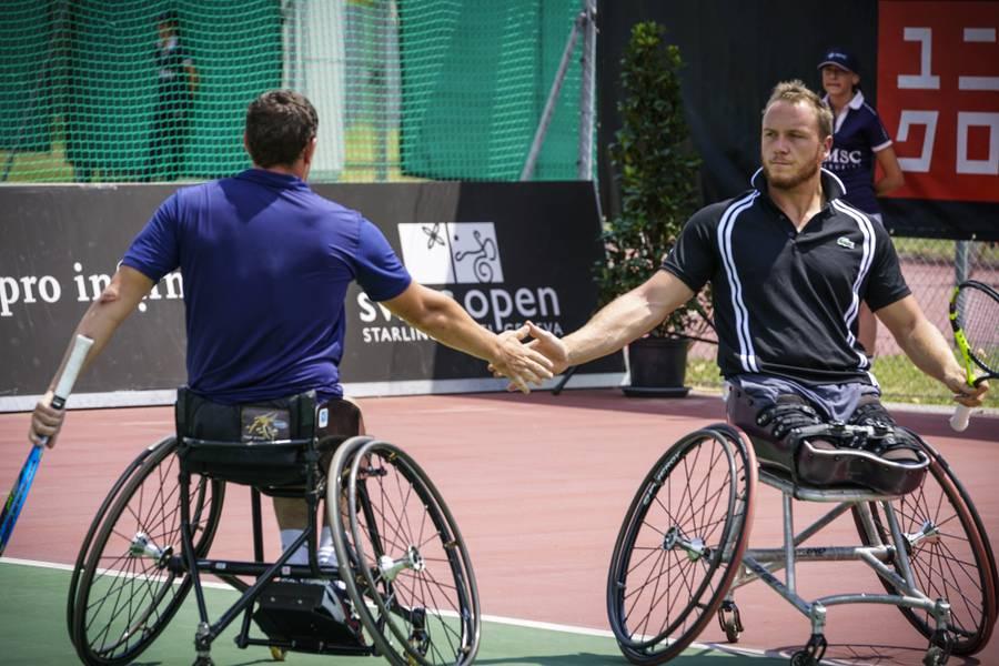 Zwei Rollstuhlfahrer geben sich einen Handschlag auf dem Tenniscourt.