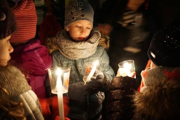 Mehrere Kinder betrachten das Licht der Kerze, die sie in den Händen halten.