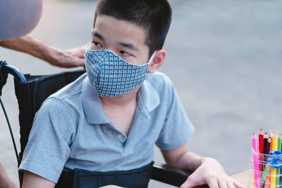 Ein Junge im Rollstuhl träget eine Schutzmaske
