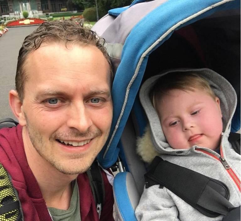 Der Vater Jonathan mit seinem Sohn Keoni, der im Kinderwagen sitzt